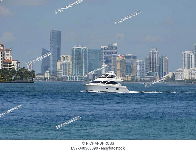 Small motor yacht on biscayne bay with downtown miami skyline in the background