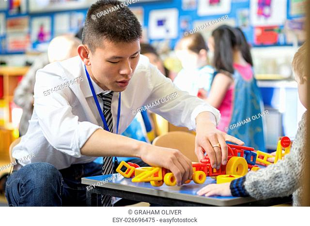 Nursery teacher is helping one of his students to make a car with building blocks