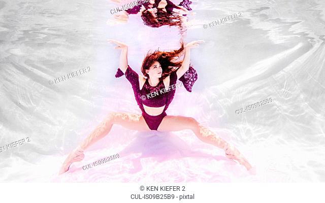 Underwater view of girl wearing purple outfit and ballet shoes, feet pointed toward floor, arms raised