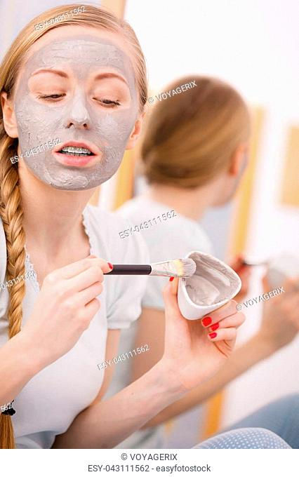 Skincare. Blonde woman in bathroom with gray clay mud mask on her face. Young lady taking care of skin. Spa beauty wellness
