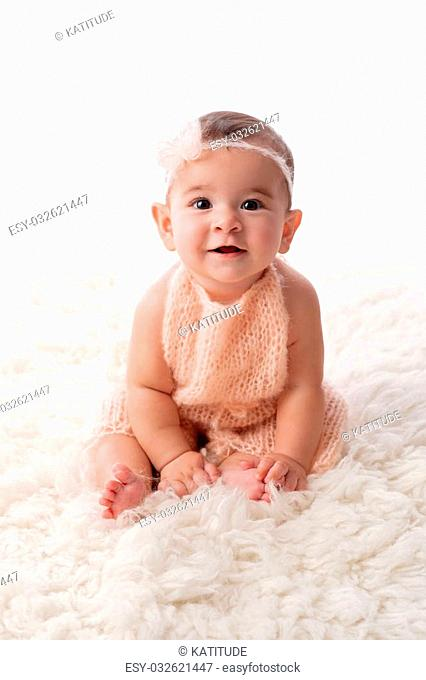 A portrait of a happy, 6 month old baby girl wearing a peach colored, knitted mohair romper. She is sitting on a cream colored sheepskin rug