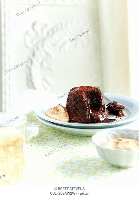 Chocolate fondant with gooey centre with cream on plate