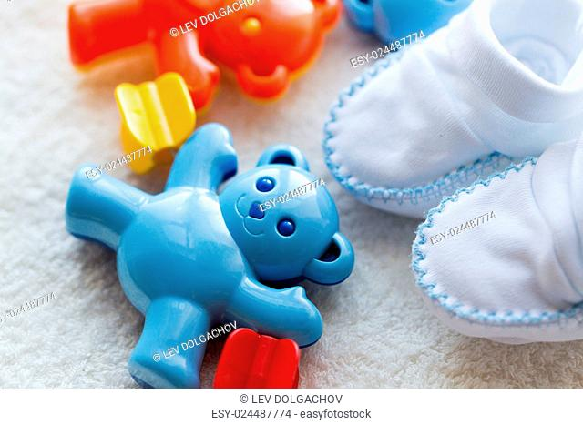babyhood, childhood, toys, clothing and object concept - close up of baby rattle and bootees for newborn boy on towel