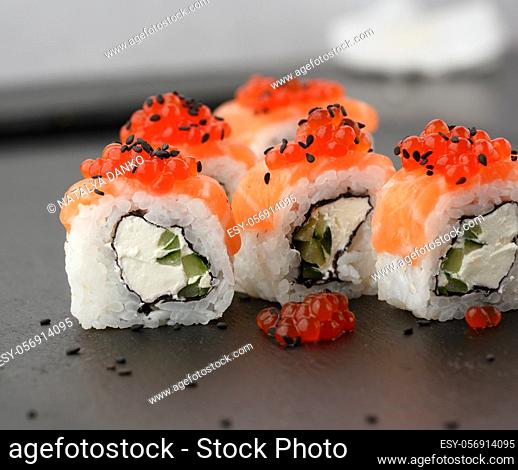 Philadelphia sushi with red caviar on a black slate board, close up