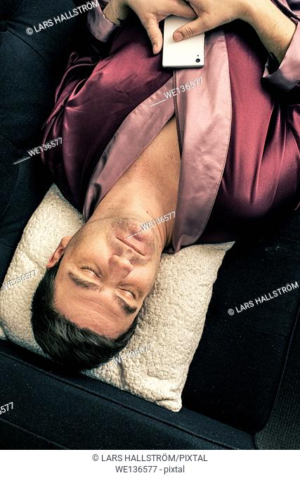 Man lying and resting on sofa at home. He is sleeping with his head on a pillow and holding a cell phone in his hands