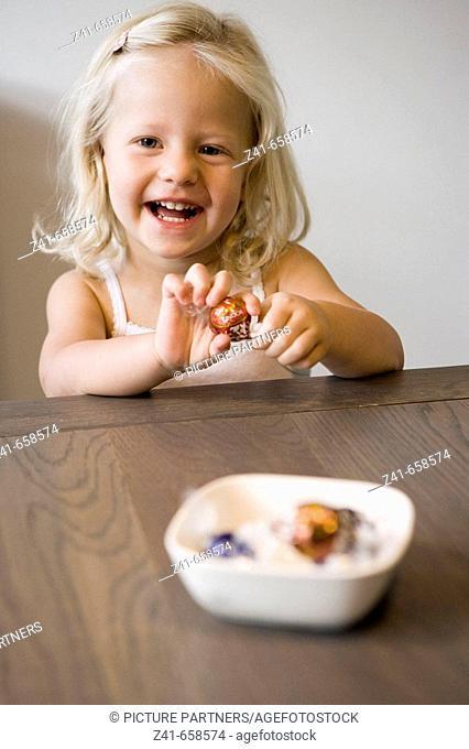 Little girl peeling a bonbon