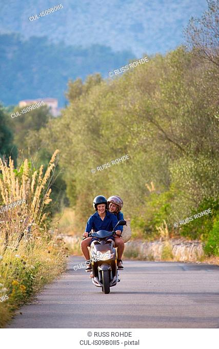 Young couple riding moped on rural road, Majorca, Spain