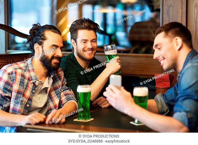 friends with smartphone drinking green beer at pub