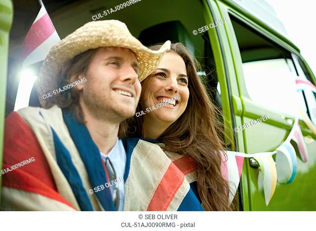 Laughing couple wrapped in flag