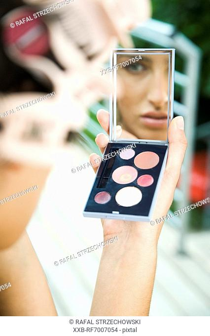 Young woman doing make up
