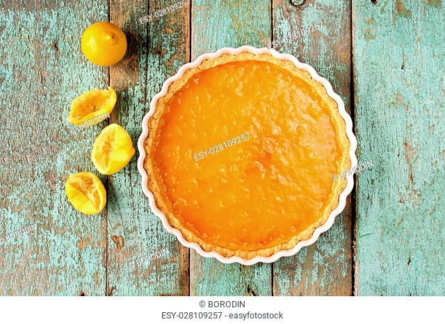 Lemon pie with fresh and squeezed lemon overhead view