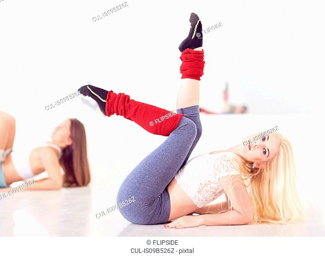 Portrait of young female ballet dancer leaning back with legs raised