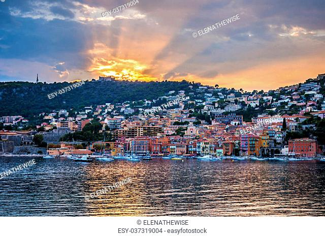 Coast view of colourful French Riviera town Villefranche-sur-Mer at dramatic sunset with sunrays reflecting in harbour