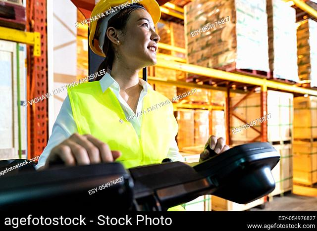 Portrait asian female warehouse worker using forklift truckin large warehouse distribution center. Business warehouse storage transportation and logistic...