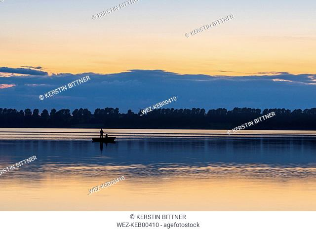 Germany, Eckernfoerde, fishermen at Windebyer Noor in the evening twilight