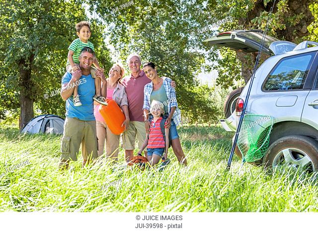 Multi-Generation Family Unpacking Car On Camping Trip
