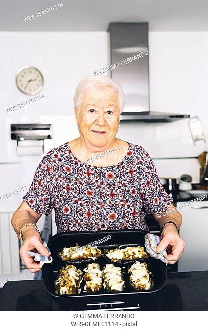 Portrait of senior woman showing prepared food in the kitchen