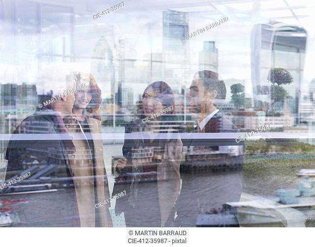 Business people talking at urban window with city view, London, UK