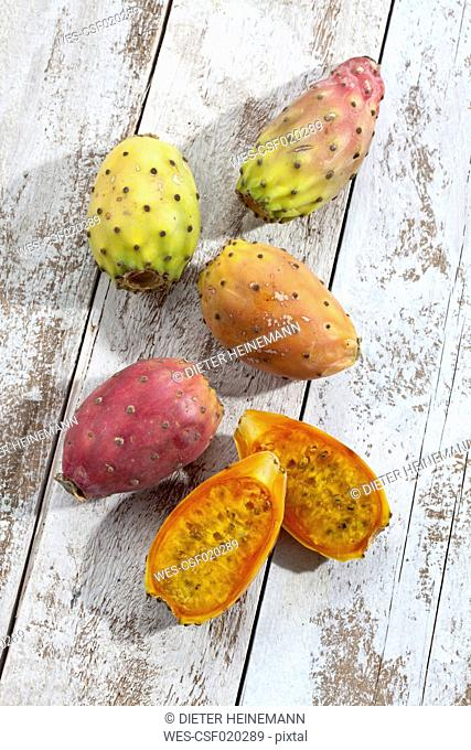 Sliced and whole prickly pears (Opuntia ficus-indica) on white wooden table, studio shot