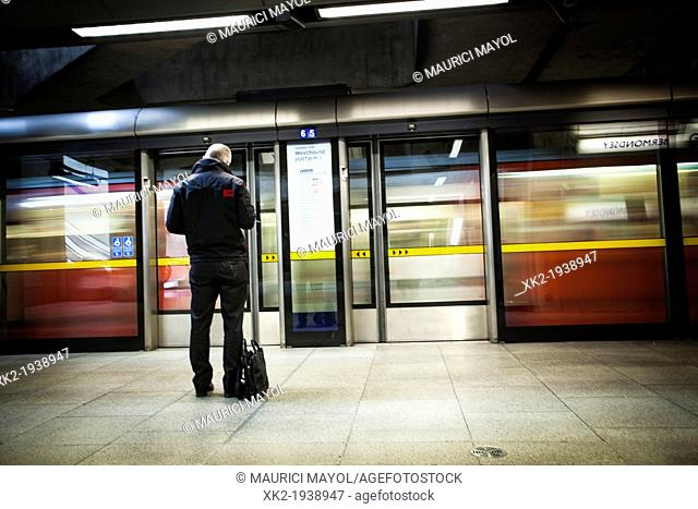 Man with a suitcase waiting for the underground in the jubilee line, Canary Wharf station, London, UK