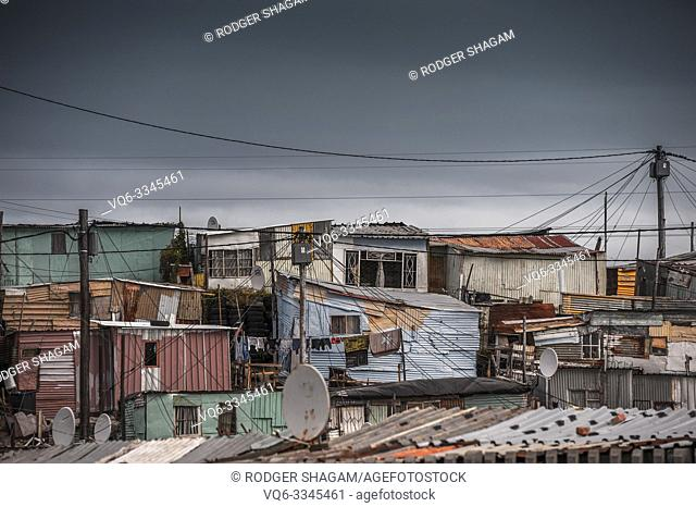 Tin, wood and cardboard. People are living here. A shambles of structures. Home to a million people or more. Cape Town, South Africa