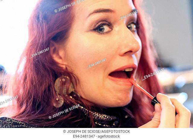 A 37 year old redheaded woman applying lip gloss looking at the camera