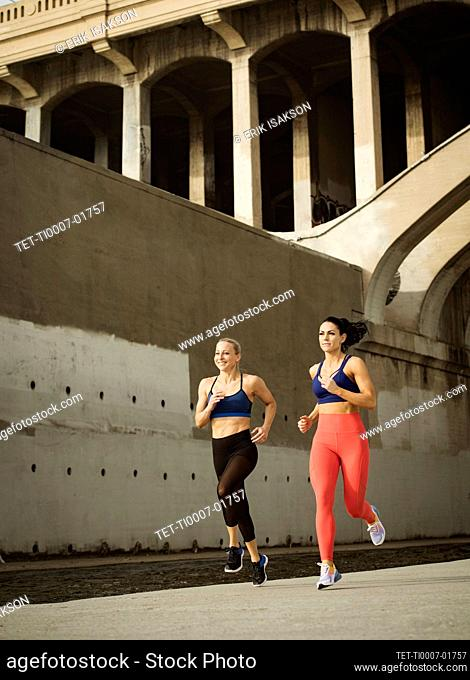 USA, California, Los Angeles, Two sporty women jogging in urban setting