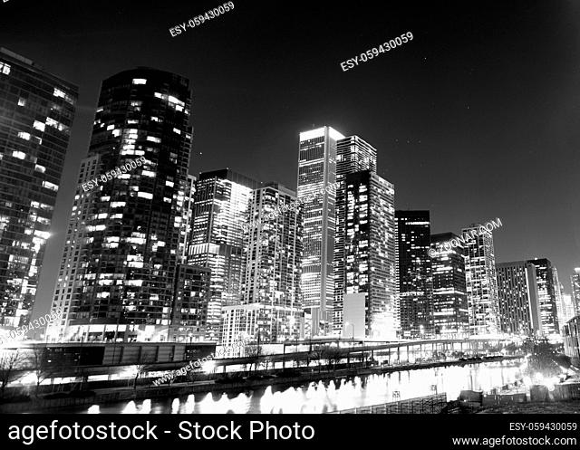 The water lights up white with reflections along the river in Chicago