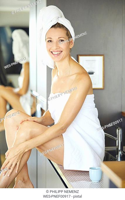Portrait of smiling woman wrapped in towels sitting on sink in the kitchen