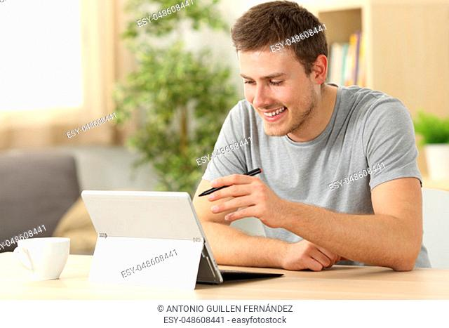 Casual man searching on line using a tablet with a pen sitting in a desk at home with a window in the background