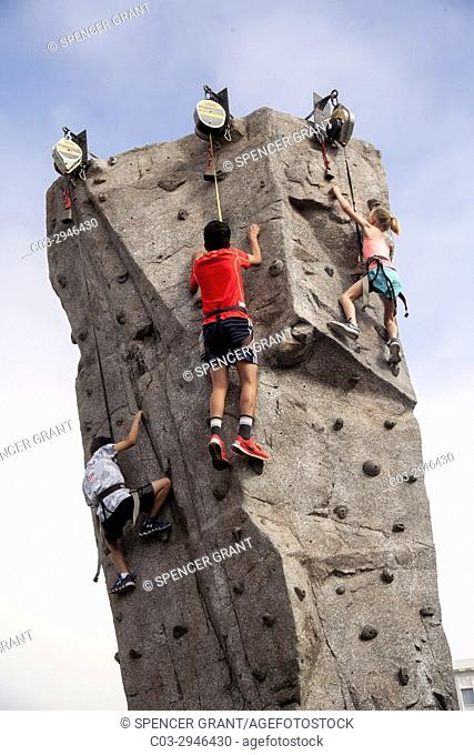 Wearing safety harnesses attached to torque reels, children climb an artificial rock needle at a festival in Newport Beach, CA