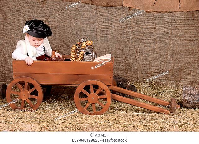 boy in national costume sits in the cart, there are bagels