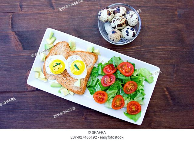 Toast with quail eggs and salad on a wooden table seen from above