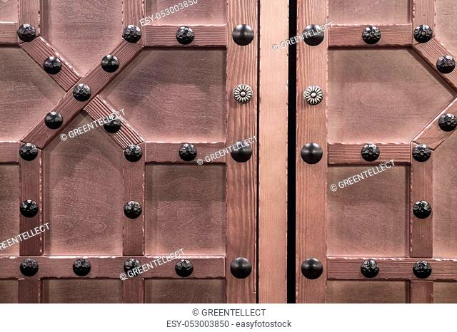 Fragment of a brown wooden door in medieval style with studded forged iron nails