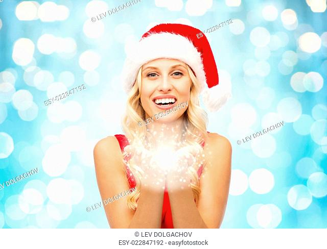 people, holidays, christmas and magic concept - happy blonde woman in santa hat holding fairy dust on palms over blue lights background