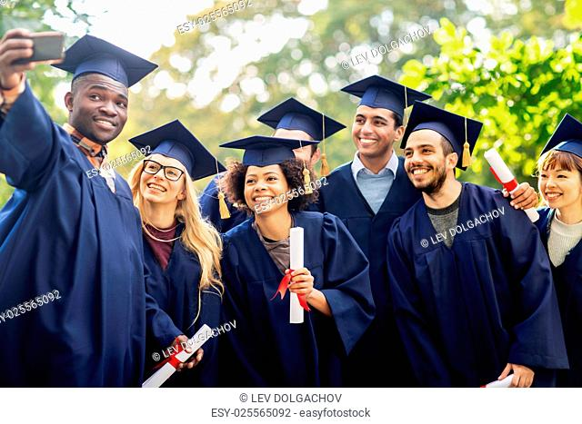 education, graduation, technology and people concept - group of happy international students in mortar boards and bachelor gowns with diplomas taking selfie by...