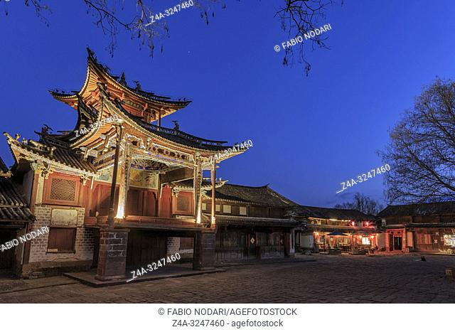 Shaxi, China - February 21, 2019: Central square of Shaxi old town at sunset with the old theater illuminated