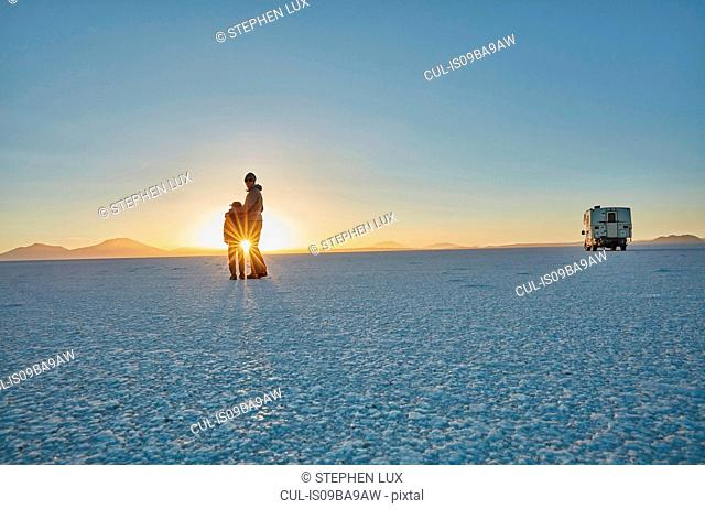 Mother and son standing on salt flats, looking at view, Salar de Uyuni, Uyuni, Oruro, Bolivia, South America