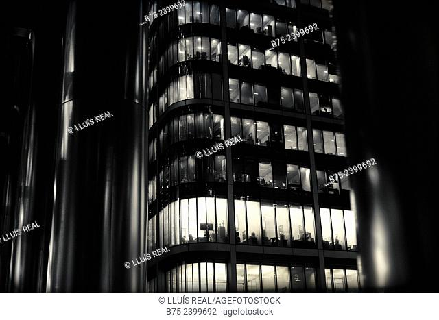 Closeup of offices buildings of modern architecture at night, with light in the windows in Canary Wharf, London, England, UK, Europe