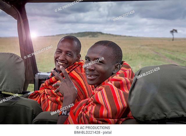 Black men smiling in car in remote field