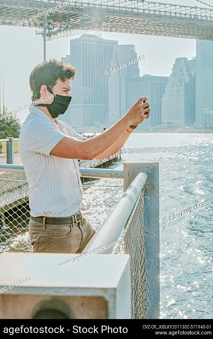 Young man by river wearing face mask with phone