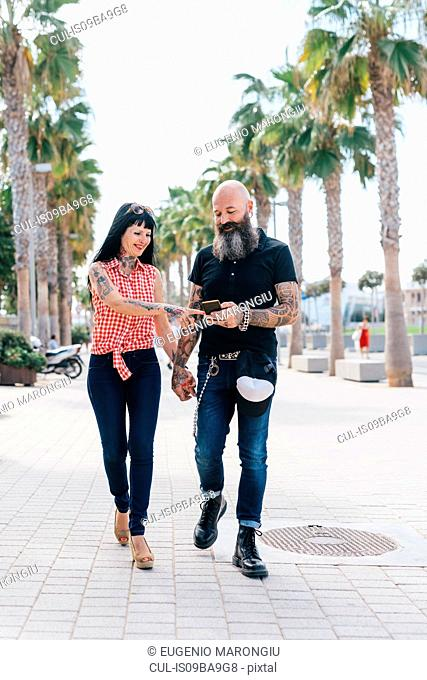 Mature hipster couple strolling while looking at smartphone on sidewalk, Valencia, Spain