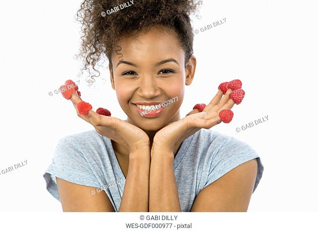 Portrait of smiling young woman with raspberries on her fingertips in front of white background