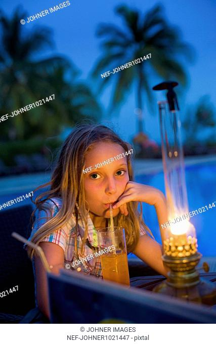 Girl sitting with drinks near swimming pool