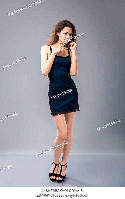 Beautiful woman standing in a black dress over gray. Studio shoot
