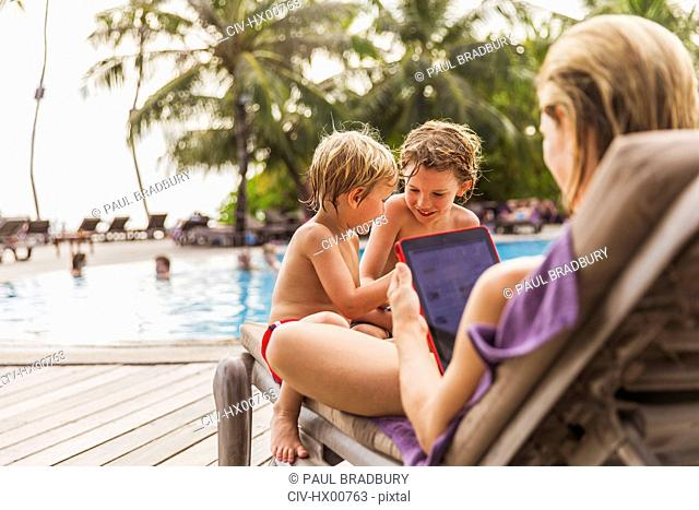 Mother and sons relaxing with digital tablet at poolside