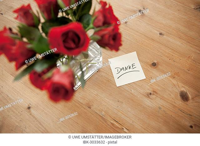 Red roses in vase with the note danke, German for thank you, Mannheim, Baden-Württemberg, Germany
