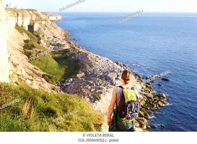 Rear view of woman with backpack looking at view of ocean, Portland, UK
