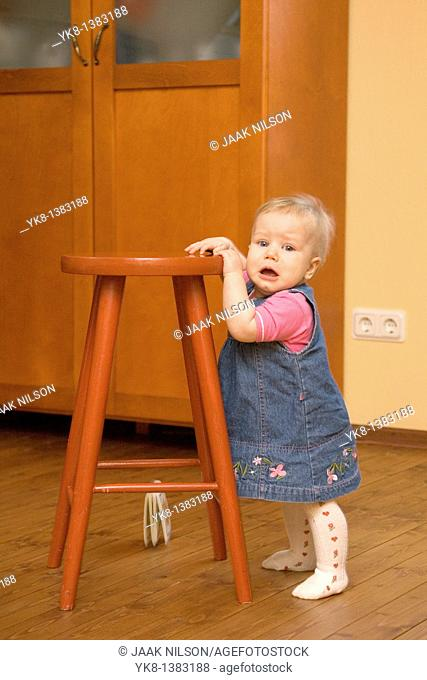 Unhappy Crying Eight Month Old Infant Girl Standing by Stool Chair