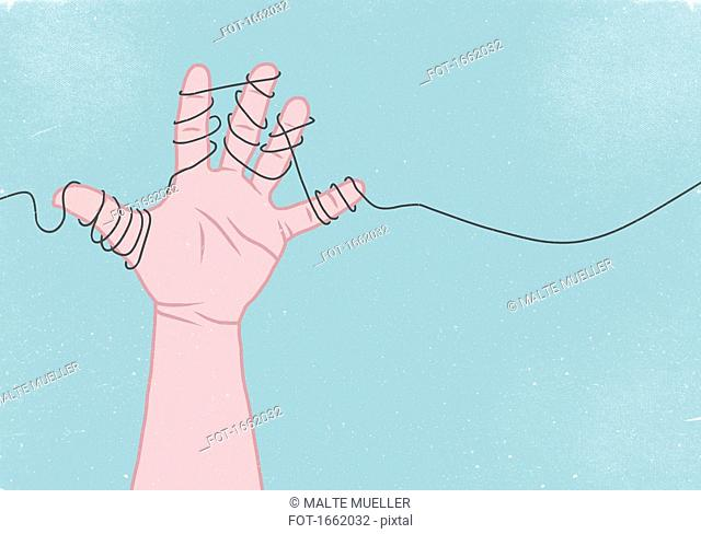 Cropped image of hand wrapped in thread against blue background